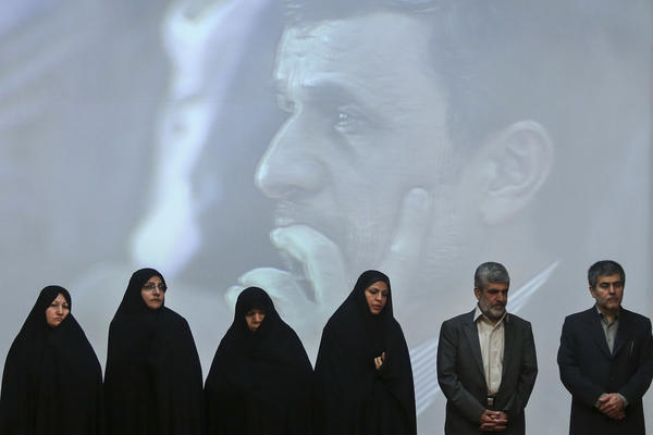 Family members of Iran's slain nuclear scientists and workers stand with the head of Iran's Atomic Energy Organization, Fereydoun Abbasi, right, Tuesday in a ceremony marking Iran's National Day of Nuclear Technology. President Mahmoud Ahmadinejad is seen on a giant screen behind them.