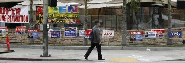 Several election signs are placed in a small strip of grass between the sidewalk and a restaurant patio on the corner of Central Avenue and Lexington Drive in Glendale.