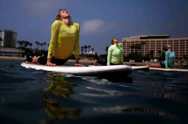 On paddle boards in Marina del Rey, Karyn Franco, 25, left, of Los Angeles and Emily Berlin, 22, and Shunti Amadi, 20, Santa Monica stretch into cobra pose.
