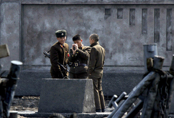 North Korean soldiers chat as they stand guard this week on the river bank of the North Korean town of Sinuiju.