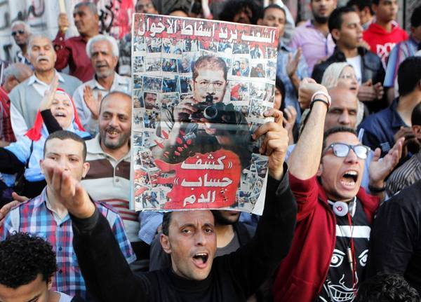 Members of Egypt's April 6 Youth Movement shout slogans against the Muslim Brotherhood and raise a poster criticizing President Mohamed Morsi at a recent rally in Cairo.