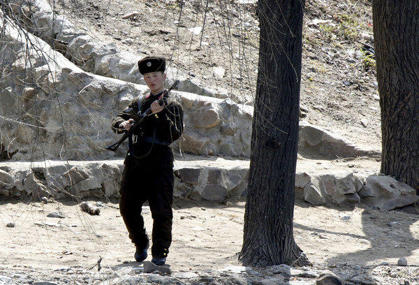 "A North Korean soldier on patrol Wednesday in the town of Sinuiju, seen from across the Yalu River from the Chinese border city of Dandong. North Korea delivered a fresh round of warmongering Thursday, claiming it had ""powerful striking means"" on standby for a missile launch."