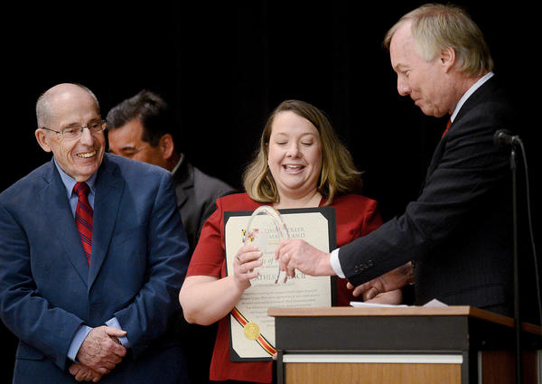 Emma K. Doub Elementary School volunteer and substitute teacher Heather Placie, center, accepted a Golden Apple award from Maryland Comptroller Peter Franchot, right, Thursday afternoon during a ceremony held in her honor in the school's all purpose room. At left is Washington County Board of Education Vice President Paul Bailey.
