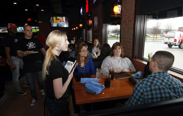 Scotty's Brewhouse server Courtney Schmidt, far left, takes orders Thursday from patrons during a family & friends soft opening at the new restaurant in the former Max & Erma's interior on North Main Street in Mishawaka. Scotty's has a formal opening on Monday.