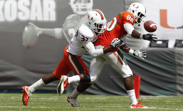 MIAMI GARDENS, FL - APRIL 14: After making the reception, Rashawn Scott #80 of the orange squad has the ball stripped away by the tackle of Ladarius Gunter #37 of the white squad during the Miami Hurricanes spring game on April 14, 2012 at Sun Life Stadium in Miami Gardens, Florida. (Photo by Joel Auerbach/Getty Images)