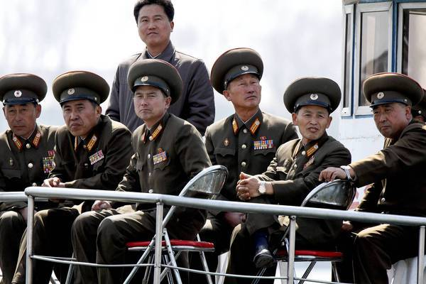 Regional intelligence officials and analysts say North Korea's planned missile launches do not appear to be in preparation for war. Above, North Korean military officers on a tour at the border with China.