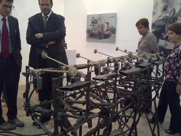 Visitors at the Zona Maco Mexico City contemporary art fair examine artist Pedro Reyes' working xylophone made out of gun parts from Mexico's drug war.