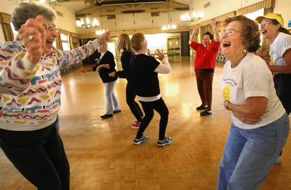 Rietta Oppenheim, left, 86, and Trudy Saltzman, 75, excel at the Laughter Yoga class in Laguna Woods.
