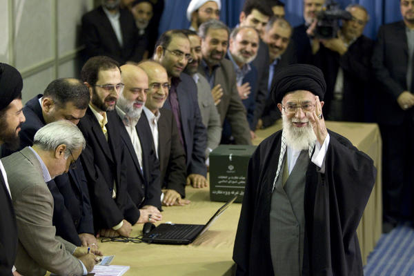Iran's Supreme Leader Ayatollah Ali Khamenei waves to the media after presenting his identification papers to cast his ballot in the parliamentary election in Tehran March 2, 2012.