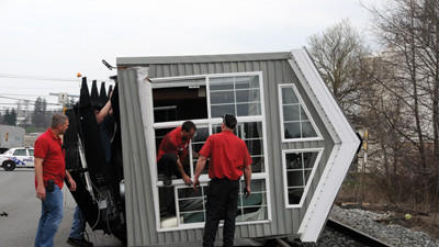 Herring Motors employees examine the mobile home that flipped over on Pleasant Avenue in Somerset Borough Thursday.