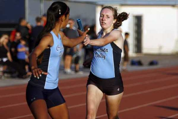 CV's Hannah Ruby, right, passes it to Grace Keller in the 4x4 relay event during a meet, which took place at Crescenta Valley High School in La Crescenta on Thursday, April 11, 2013. (Cheryl A. Guerrero/Staff photographer)