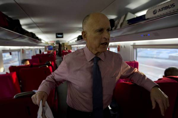 Gov. Jerry Brown speaks to journalists aboard a sleek high-speed train leaving the Beijing South station in China. The governor would like to see China, which is enjoying an economic boom and spent $77.6 billion on overseas investments last year, pump some of its cash into California's troubled bullet-train project.