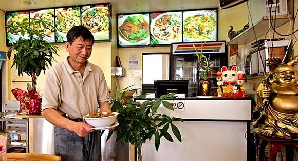 Happy Kitchen's owner and chef, Jixian Liang, prepares to serves a specialty of the house.