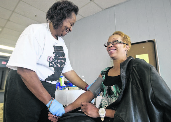 Nurse Betty Greene, left, checks the blood pressure of South Bend resident Anita Nelson during last year's Indiana Black Barbershop Health Initiative at Image Hair Studio in South Bend. This year's event is Saturday.