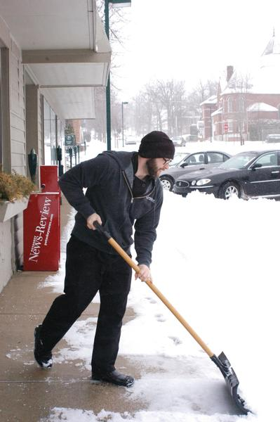 Eric Leech shovels snow off the sidewalk in front of The Bistro in Petoskey Friday. I dont remember it being this long, he said of the winter weather that has stretched into mid-April.