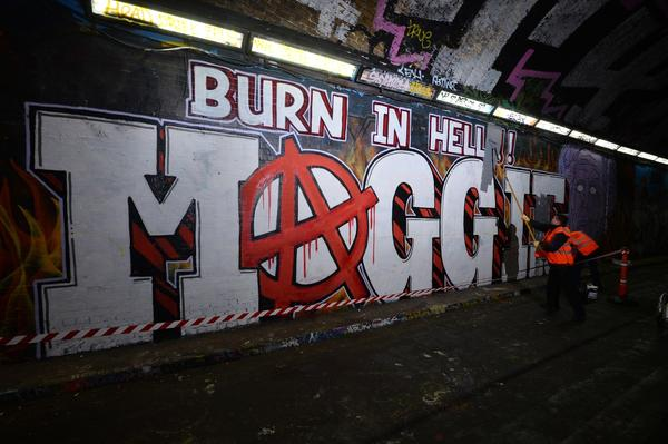 "Workers paint over grafitti that reads ""Burn in hell Maggie,"" referring to Britain's late ex-Prime Minister Margaret Thatcher, in London on Friday."