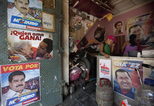 A boy stands inside his family's food stand in Caracas, which is adorned with campaign election posters for acting President Nicolas Maduro.