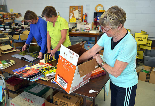 Volunteers from left, Carol Brashears, Susan Latimer and Jeanne Stoner unpack books Monday for the American Association of University Women Used Book Sale that opens Thursday at Arc of Washington County. This is the 50th anniversary of the fundraising sale.
