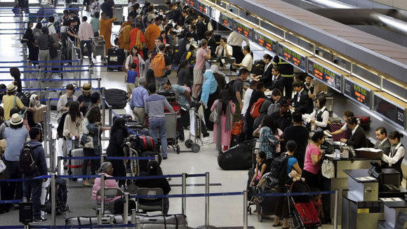 Travelers check in for their flights at Los Angeles Intenational Airport in a June file photo.