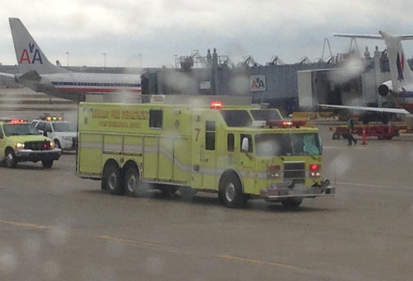 An airport fire truck is seen from the window of American Airlines Flight #153 from Orlando, which landed on Runway 28 at O'Hare International Airport. Due to a mechanical issue, the aircraft could not taxi to the gate.