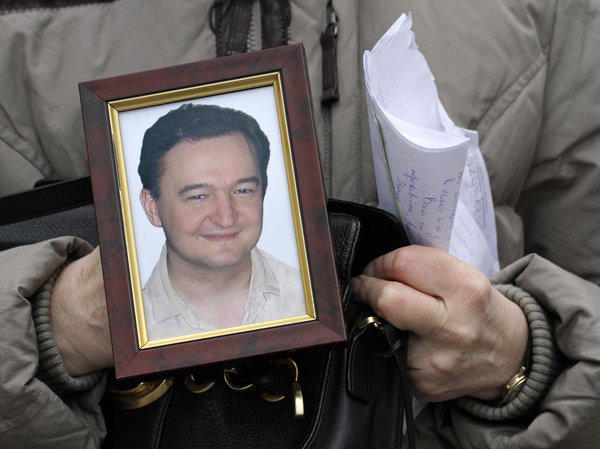 In a file photograph from 2009, Nataliya Magnitskaya holds a photo of her son, Russian lawyer Sergei Magnitsky, who died in custody that year. The U.S. has named 18 Russians to be penalized for alleged human rights abuses under a law named for Magnitsky.