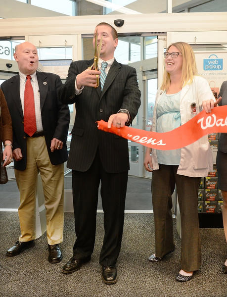 Walgreens store manager Dennis Bower, center, gets a reaction from Hagerstown City Councilman Don Munson, left and store pharmacy manager Natalie Logsdon after cutting a ribbon to open the Dual Highway store Friday morning.