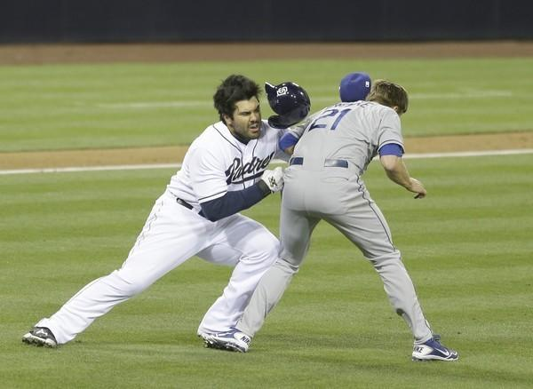 San Diego Padres' Carlos Quentin charges into Los Angeles Dodgers pitcher Zack Greinke after being hit by a pitch in the sixth inning of baseball game in San Diego.