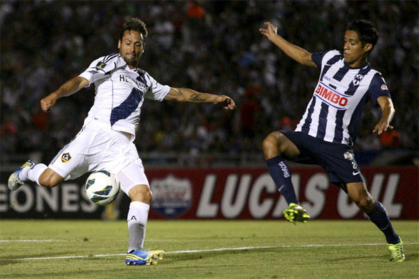 Galaxy's Todd Dunivant, left, prepares to kick a shot as Monterrey's Severo Meza attempts to block during a CONCACAF Champions League semi-final soccer match.