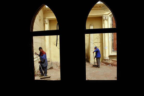 Workers clean up debris in the aftermath of sectarian violence between Muslims and Coptic Christians outside St. Mark's Cathedral in Cairo last weekend. One Copt died in bursts of tear gas, gunfire and gasoline bombs.