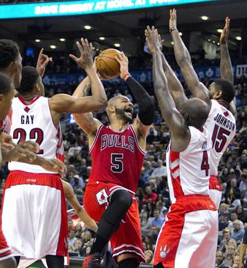 Carlos Boozer drives to the basket past the Raptors' Rudy Gay, Amir Johnson and Quincy Acy in the first half.