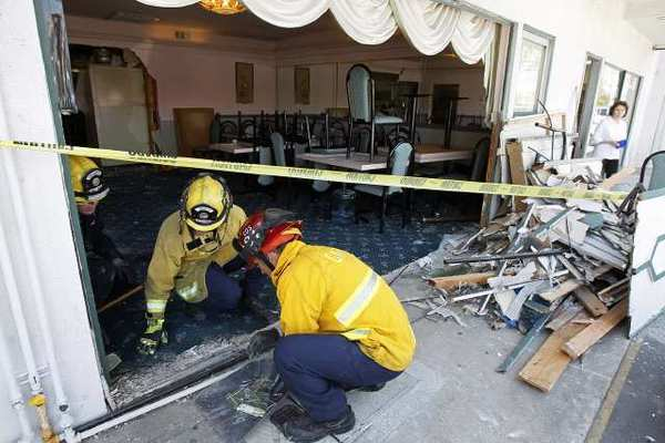 Costa Mesa firefighters clean up debris after a woman drove her car into the Golden Garden Restaurant on Friday.