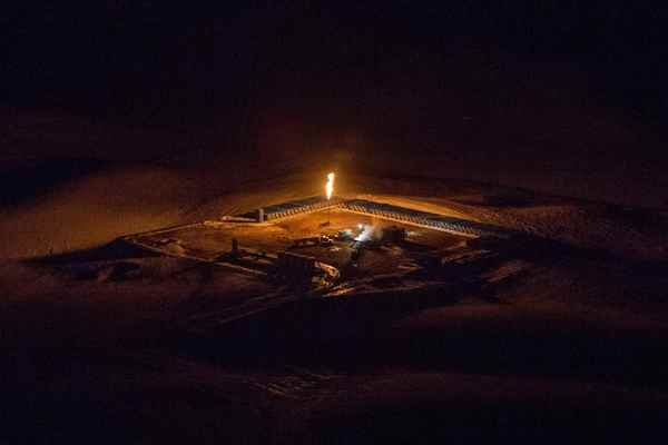 An aerial image shows a natural gas flare after sunset outside of Williston, North Dakota March 12, 2013.