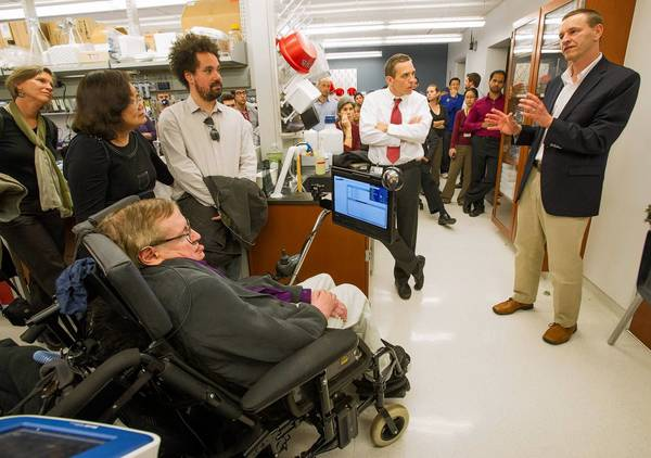 Cosmologist Stephen Hawking, who has ALS, listens to a presentation by Dr. Robert Baloh during a tour of the Cedars-Sinai Regenerative Medicine Institute, which studies the disease. At center is the director, Clive Svendsen.