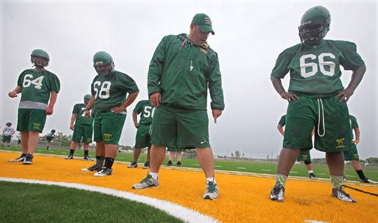 Presentation College football coach Andy Carr gives instructions to some players during fall practices last season. The Saints are currently participating in spring football workouts. American News File Photo by John Davis