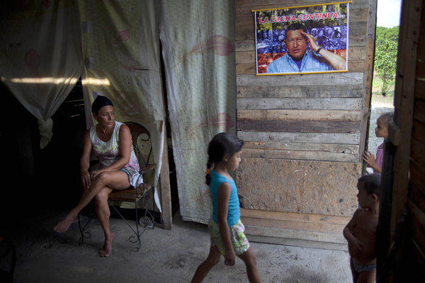 Yadaira Nunez, 43, sits in her wooden shack next to a poster of Venezuela's late president, Hugo Chavez, at a squatter settlement near Tacarigua, Venezuela.