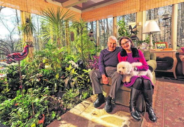 Leonard Sachs, left, and Lainy LeBow-Sachs relax with their puppy, Ozzie, in the sunroom of their Stevenson, Maryland home, a contemporary stone, glass and wood home that brings nature indoors. (Amy Davis/Baltimore Sun/MCT)