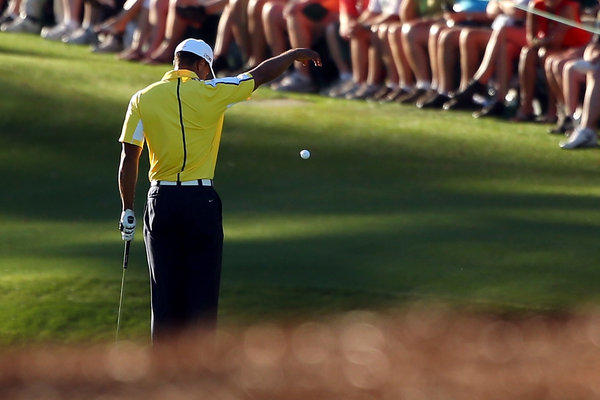 Tiger Woods drops his ball after he hits it into the water on the 15th hole during the second round of the 2013 Masters Tournament at Augusta National Golf Club in Augusta, Ga.