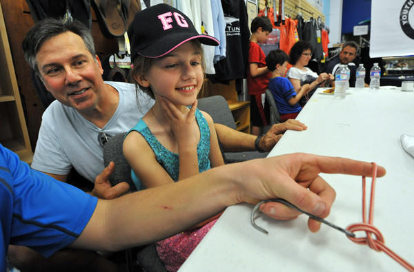 "Anna Estremsky, 9, wearing her ""FG"" (Fisher Girl) cap, and her father, Gary Estremsky, left, watch Ryan Dean demonstrate a Palomar knot at the Youth Angler Club of the Maryland Saltwater Sportfishing Association."