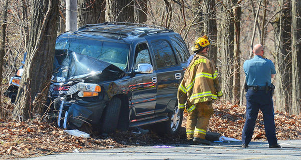 A Leitersburg Volunteer firefighter and a Washington Co. Sheriff's Deputy wait for a tow truck to remove an SUV after the driver lost control and careened into a tree on Pen Mar Road Saturday afternoon. The driver was airlifted.