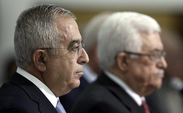 Palestinian Authority Prime Minister Salam Fayyad, left, on May 16, 2012 with President Mahmoud Abbas during the swearing in of a new Cabinet in the West Bank town of Ramallah.