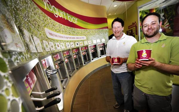 Richard Ryan, center, and his son Kevin Ryan pose at the yogurt bar at their new Menchie's in the Airport Center Shopping Center. The owners are the same people who opened that one at The Shops at Cedar Point in Allentown last year.