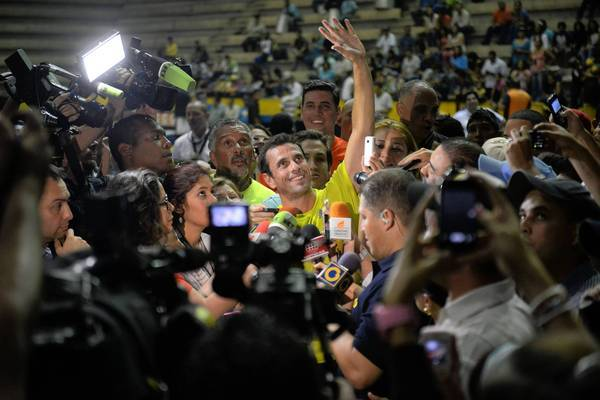Venezuelan opposition candidate Henrique Capriles is surrounded by journalists Friday after playing basketball during a nonpolitical event in Caracas. Voters will head to the polls Sunday.