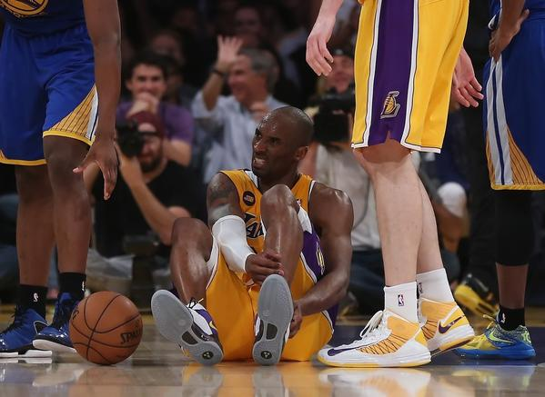 Kobe Bryant holds his lower leg after suffering an apparent injury during the second half of the Lakers' 118-116 win over the Golden State Warriors.