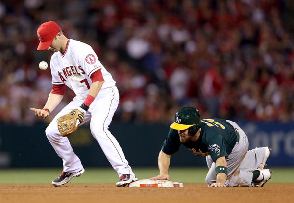 Angels shortstop Andrew Romine bobbles the ball as Oakland A's catcher Derek Norris steals second base.