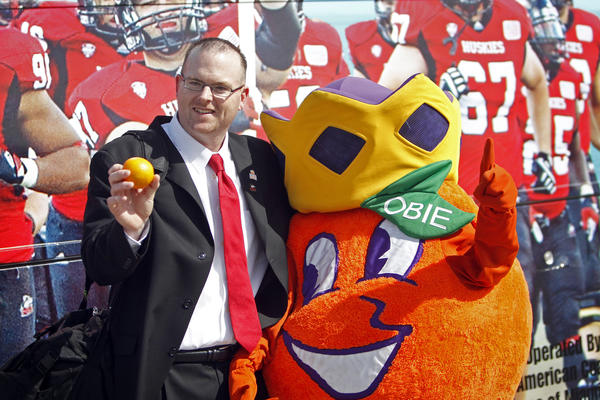 North Illinois coach Rod Carey poses for a photo with Obie, as the team arrived for their game against Florida State in the Orange Bowl.