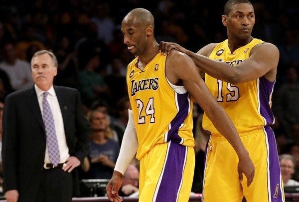 Lakers forward Metta World Peaces gives guard Kobe Bryant a pat on the back as Bryant limps off the court after making two free throws following a foul and Achilles' tendon injury.