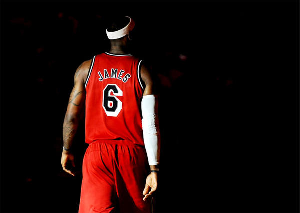 Miami Heat forward LeBron James fades into the dark during team introductions before a game against the Portland Trail Blazers.