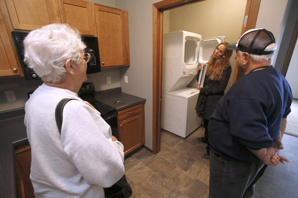 Christi Barrus, property manager at Dakota Estates, center right, talks about the washer and dryer as Patricia and Allen Wald walk through their new apartment Friday. American News Photo by John Davis