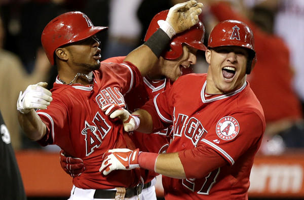 Angels teammates Luis Jimenez, left, Josh Hamilton, center, and Mike Trout celebrate after Albert Pujols drove in Jimenez and Trout to defeat the Houston Astros on Saturday night in Anaheim.