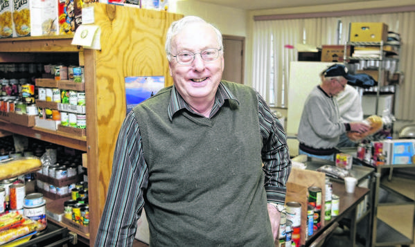 Volunteers work behind the Rev. Warren Kirkwood at the Mishawaka Alliance of Care Food Pantry, which he's led for 20 years at Albright United Methodist Church in Mishawaka. He'll retire from the job on July 1.